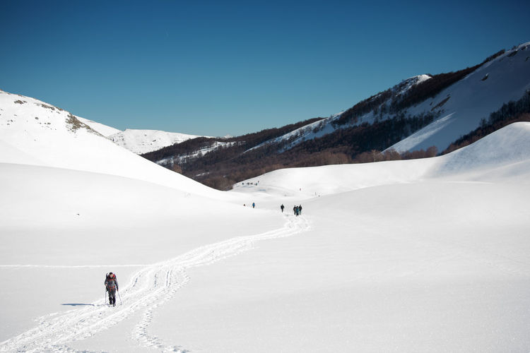 Man walking on snowcapped mountain against clear sky