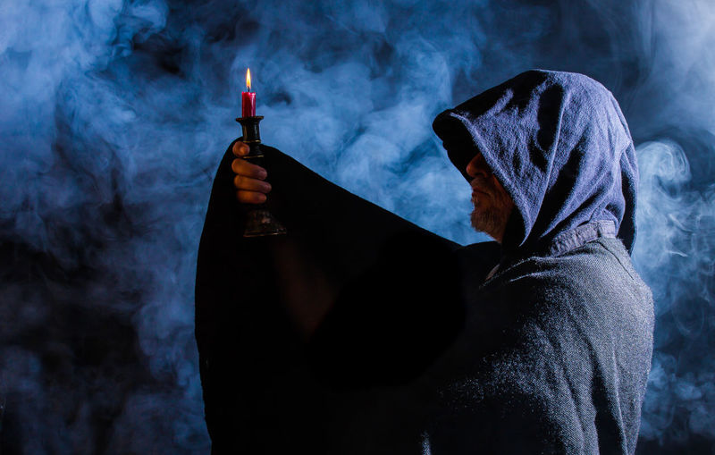 a man with a hood holds a candle holder in his hand Abbott Candle Candlestick Church Dark Faith Fear Halloween Suppression Cape  Ceremony Cult Leader Fog Foggy Hood Mystical Priest Religion Scary Sect Spooky Superstition