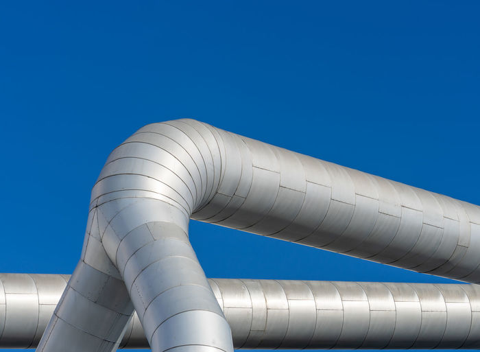 Low angle view of silver pipes against clear blue sky