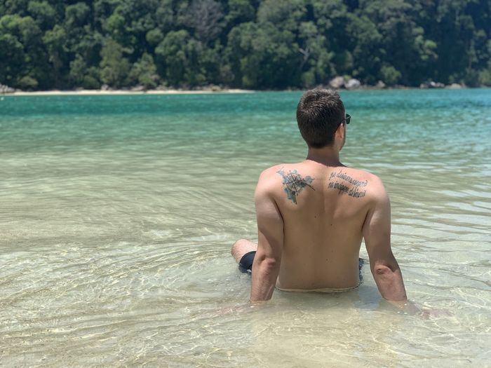 Rear view of shirtless man in sea