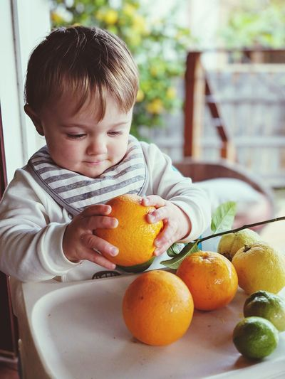 Cute boy holding orange fruits while sitting at home