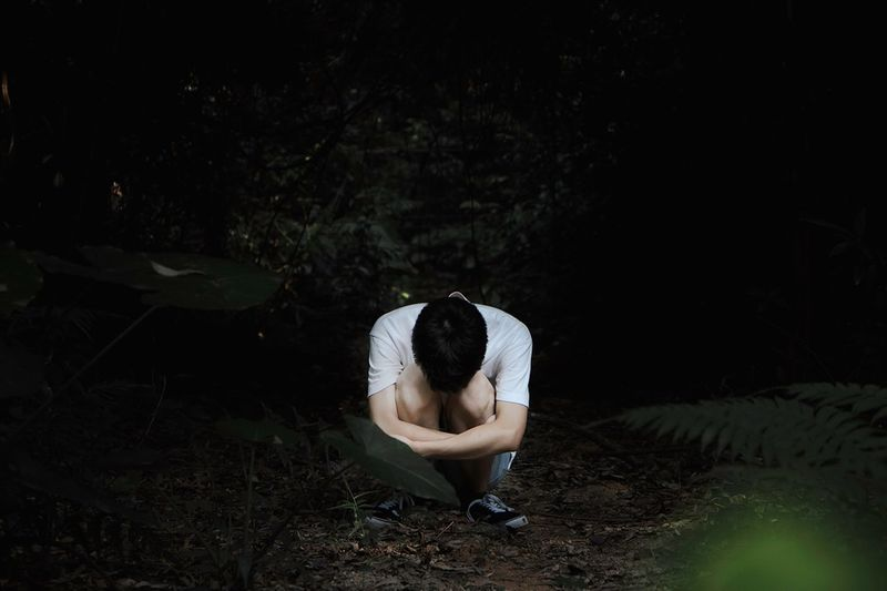 Man Crouching In Forest