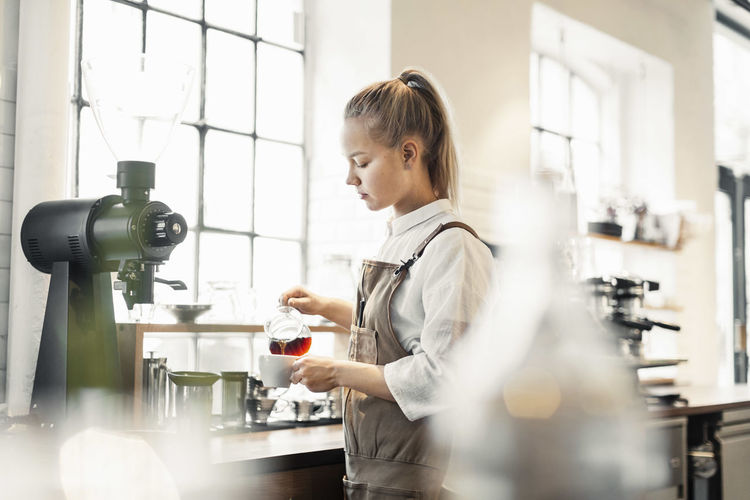 Side view of woman working in kitchen