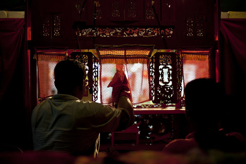 Rear view of people sitting in temple