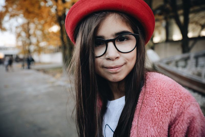Portrait Of Smiling Girl With Long Hair Wearing Eyeglasses And Hat While Standing In Park During Autumn