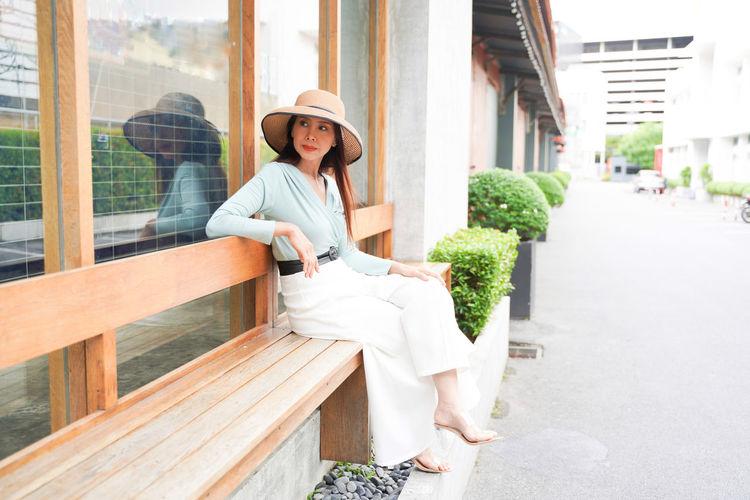 Portrait of woman sitting outside building