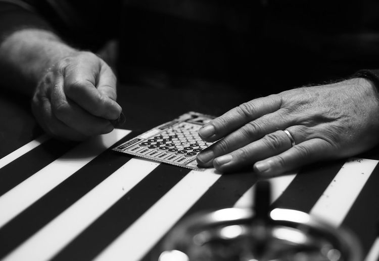 Close-up of man scratching lottery ticket