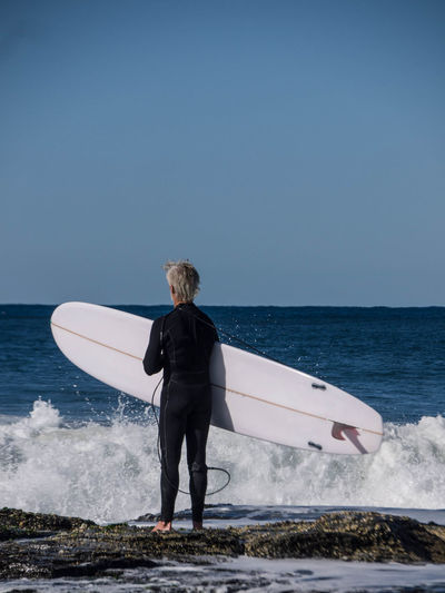 Carrying Clear Sky Crash Day Deep In Thought Full Length Holding Horizon Over Water Leisure Activity Lifestyles Nature Older Man One Man Only One Person Only Men Only Women Outdoors Real People Rear View Sea Sky Standing Surfer Water Waves