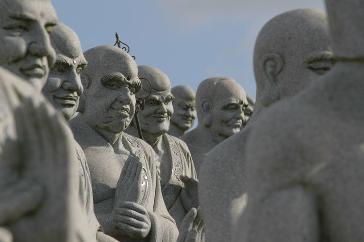 Close-up of buddha statues against sky