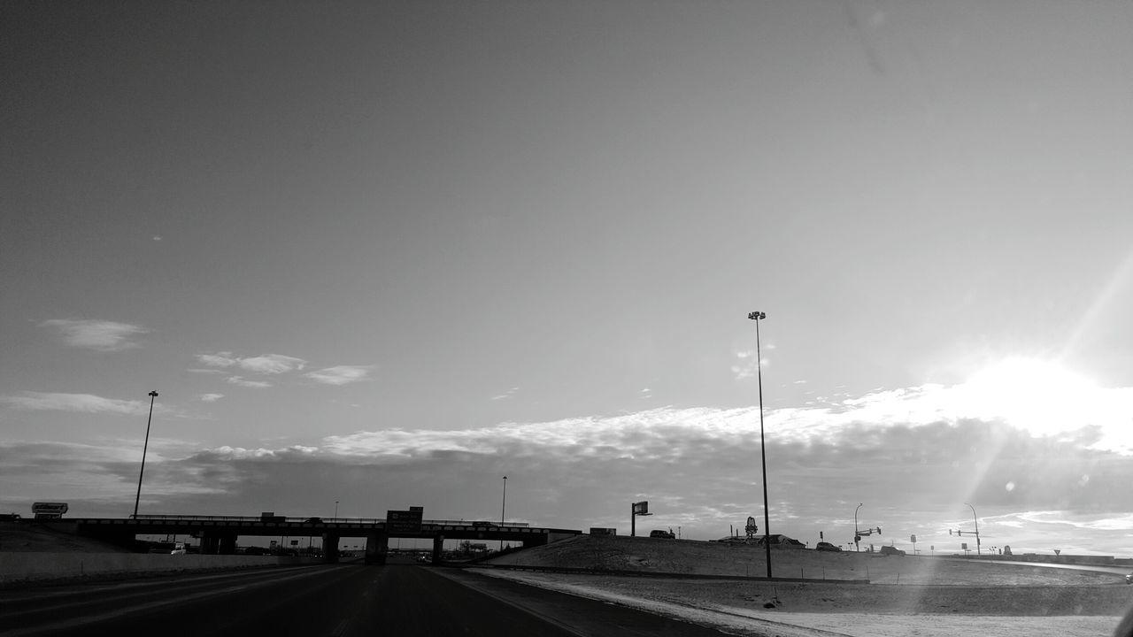 Street By Field Against Sky