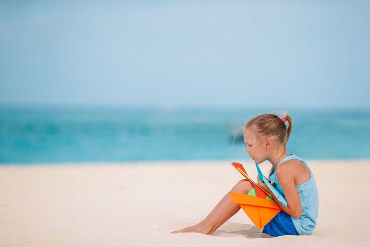 Boy toy on sand at beach against sky