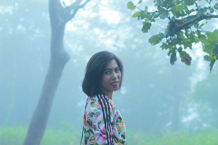 Portrait of smiling woman standing in forest during foggy weather