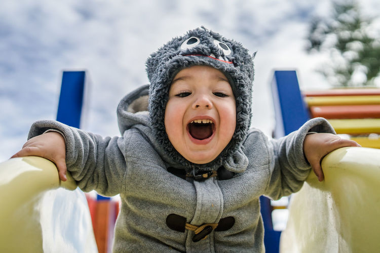 Low angle portrait of happy baby boy screaming while sliding against sky at playground