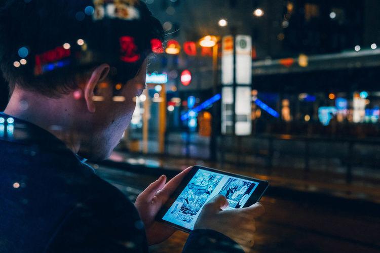 Close-up of man using mobile phone at night
