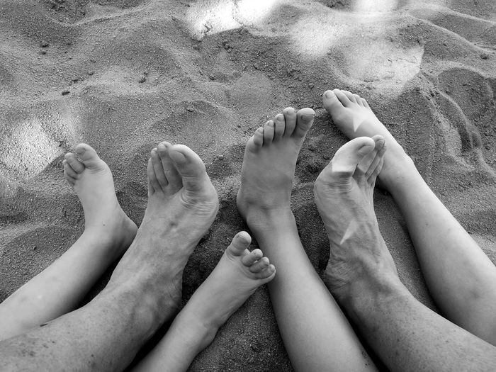 Low section of people with barefoot resting on sand at beach