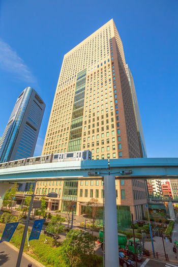 Tokyo, Japan:Tokyo urban businessmen commuter walking in Shiodome, an area with high skyscrapers in Shinbashi Financial District.Yurikamome monorail at Shiodome Station. Daylight shot Wide angle view of elevated monorail train to Daiba, passing between Shiodome skyscrapers in Shimbashi Financial district in Tokyo, Japan. Japanese white-collar workers walking in Shiodome City Center area.Business people commuter in Shinbashi Financial District. Wide angle view. Corporate cityscape concept Business Cityscape Commuter Financial District  Financial District, London Japanese  People Watching Shinbashi Station Skyscrapers Tokyo Tokyo,Japan Walking Around Architecture Blue Building Building Exterior Built Structure Businessmen Businessmen Walking City Day Glass - Material Low Angle View Modern Nature No People Office Office Building Exterior Outdoors People Shinbashi Shinbashi, Tokyo Shiodome Sky Skyscraper Sunlight Tall - High Tower