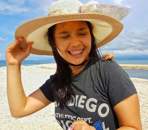 Smiling Young Woman Looking At Crab On Shoulder