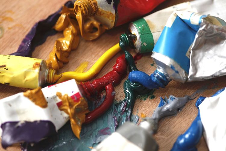 High angle view of colorful paints with tubes on table at workshop
