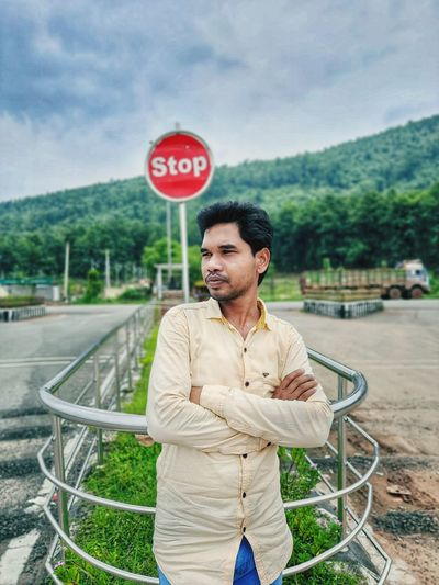 An indian young man standing at the traffic chowk in front of stop signal.