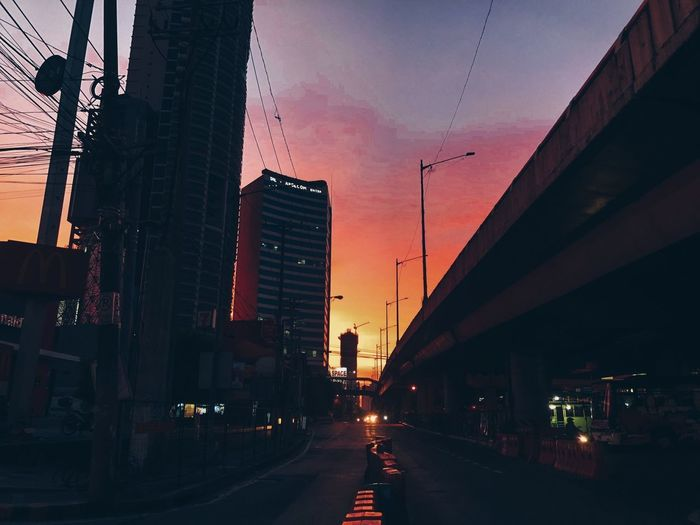 Street amidst buildings against sky at sunset