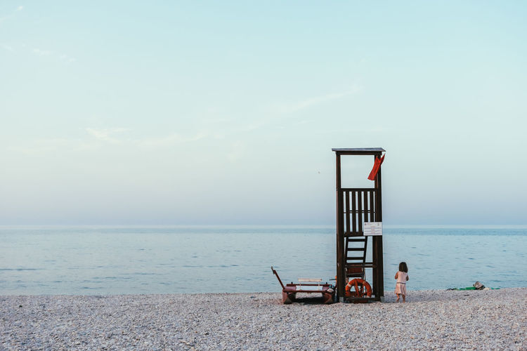Girl standing by lifeguard hut against sea at beach