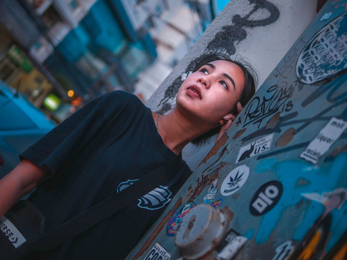 Woman looking away while standing by graffiti