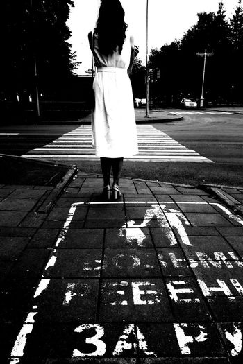 City Crosswalk Day Footpath Full Length Leisure Activity Lifestyles Marking One Person Outdoors Paving Stone Real People Rear View Road Road Marking Standing Street Symbol Transportation Walking Women
