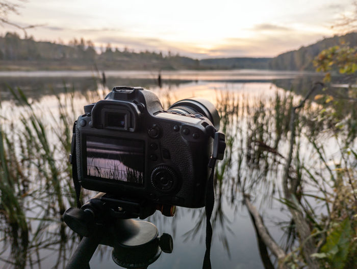 Close-up of camera on lake against sky during sunset