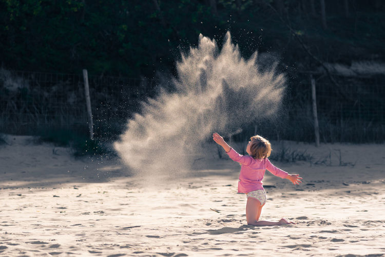 Little girl playing on a beach and throwing handful of sand up in the air Adult Childhood Day Full Length Fun Illuminated Leisure Activity Motion Nature One Person Outdoors People Pink Color Real People Spraying Sun Light Live For The Story Place Of Heart