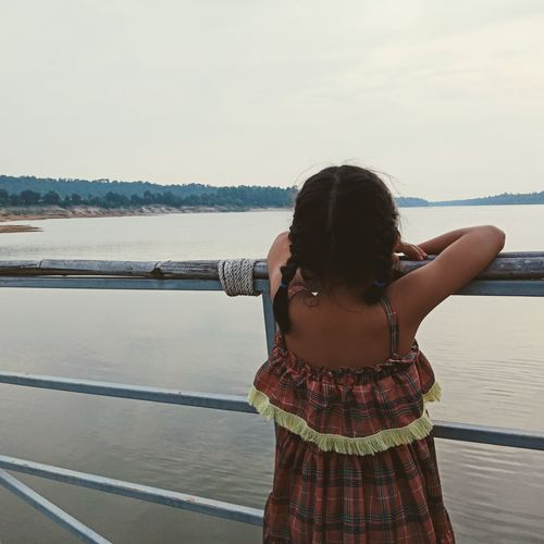 Rear view of girl standing by railing against sea