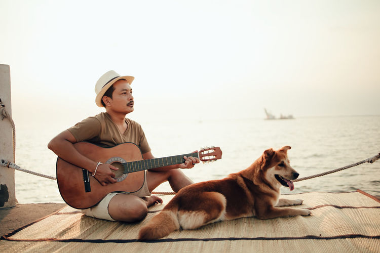 Man playing guitar sitting with dog against sea