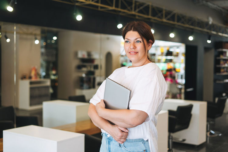 Beautiful stylish young woman plus size body positive with laptop at the beauty salon office