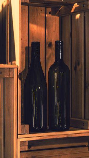 Close-up of beer bottles on wooden shelf