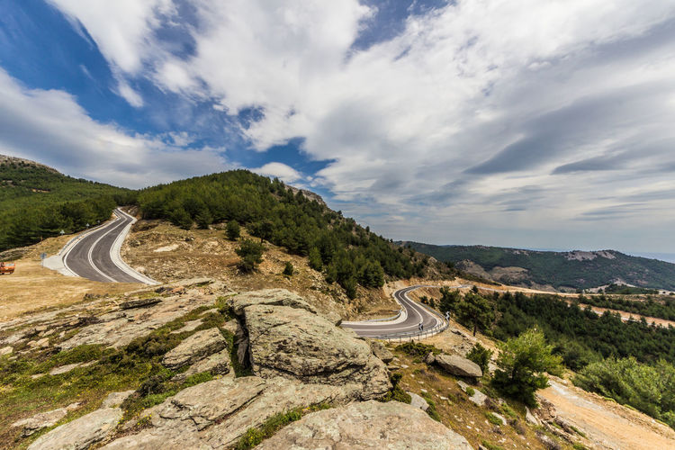 High angle view of winding road against cloudy sky