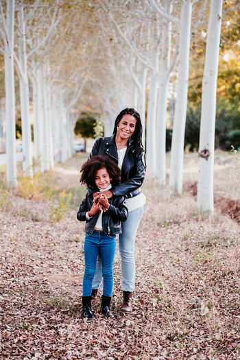 Full length portrait of mother and daughter standing by tree at park