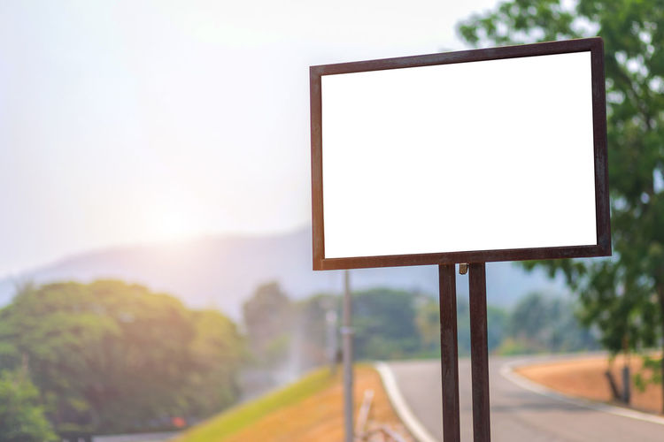 Advertisement Billboard Blank Communication Copy Space Day Empty Focus On Foreground Message Nature No People Outdoors Placard Plant Road Sign Sky Sport Street Sunlight Tree
