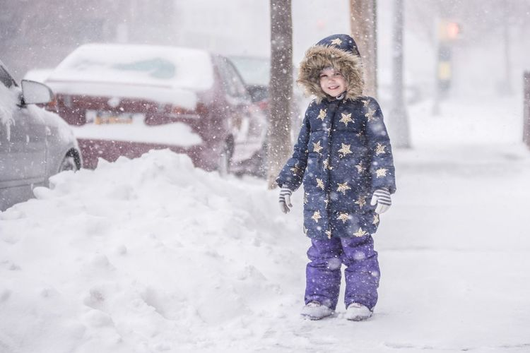 Portrait of smiling child standing on snowy sidewalk