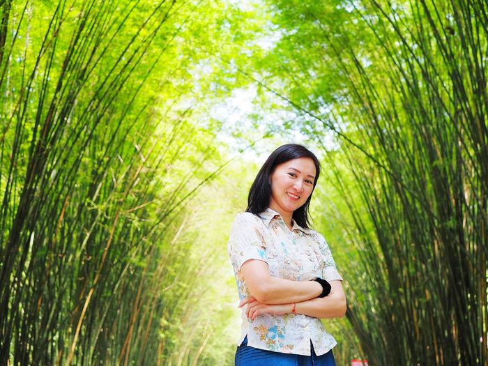 Smiling Woman Standing By Plants
