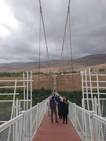 Railing Connection Bridge - Man Made Structure Footbridge The Way Forward Sky Men Walking Long Full Length Rear View Person Wood Paneling Narrow Wooden Tourist Cloud - Sky Casual Clothing Mammal Suspension Bridge
