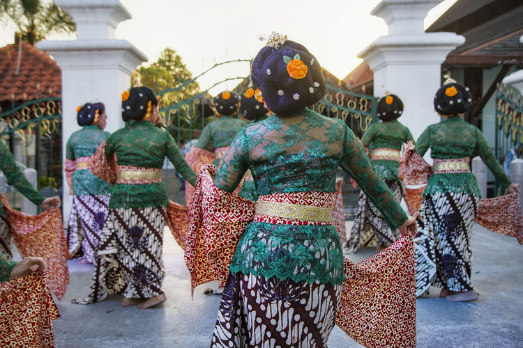 Group of women wearing traditional clothing while dancing in city