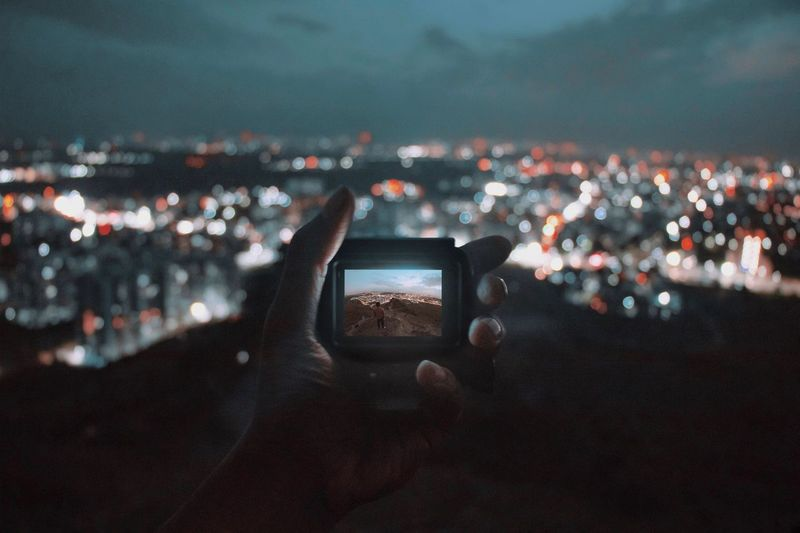 Man photographing illuminated cityscape against sky at night