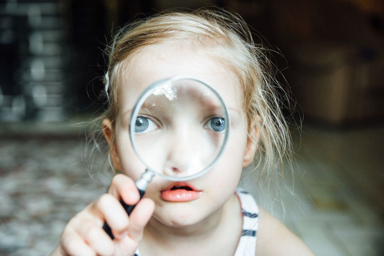 Close-up portrait of girl looking through magnifying glass