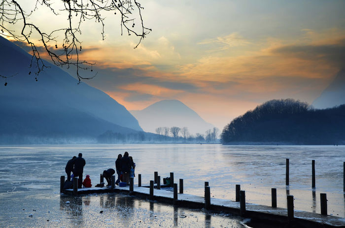 People on a pier on a frozen lake with mountain in sunset in Lombardy, Italy. Beauty In Nature Branch Cloud - Sky Cold Temperature Dawn Dusk Ice Ice Lake Many People Mountain Mountain Range Nature Orange Sky Outdoors People Pier Real People Scenics Silhouette Snow Sunset Tranquility Unrecognizable People Water Winter