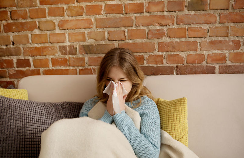 Young woman blowing nose while sitting on sofa at home
