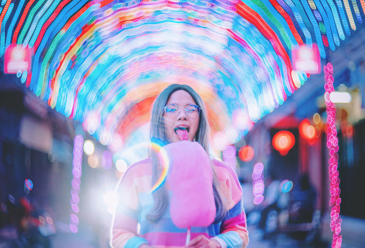 Woman eating cotton candy while standing against illuminated wall at night
