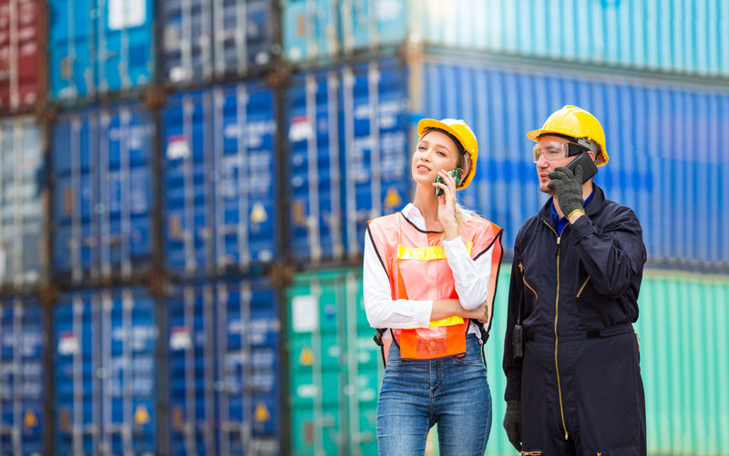 Engineers are using mobile phones in the port of loading goods.