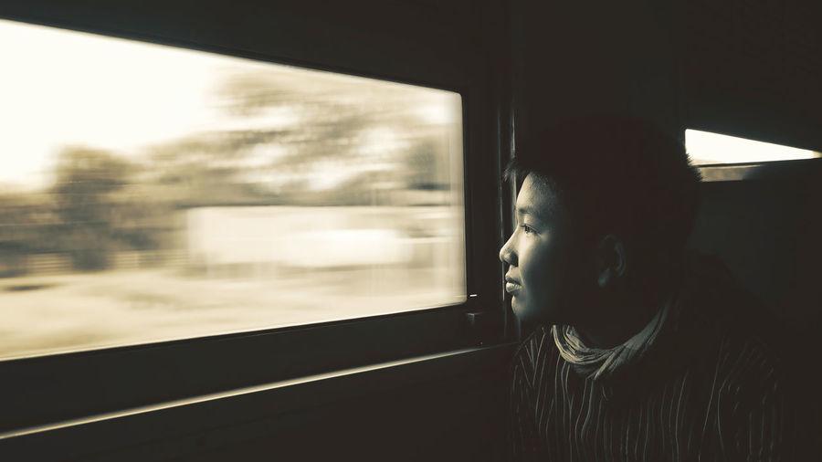 Cute boy looking towards window in train