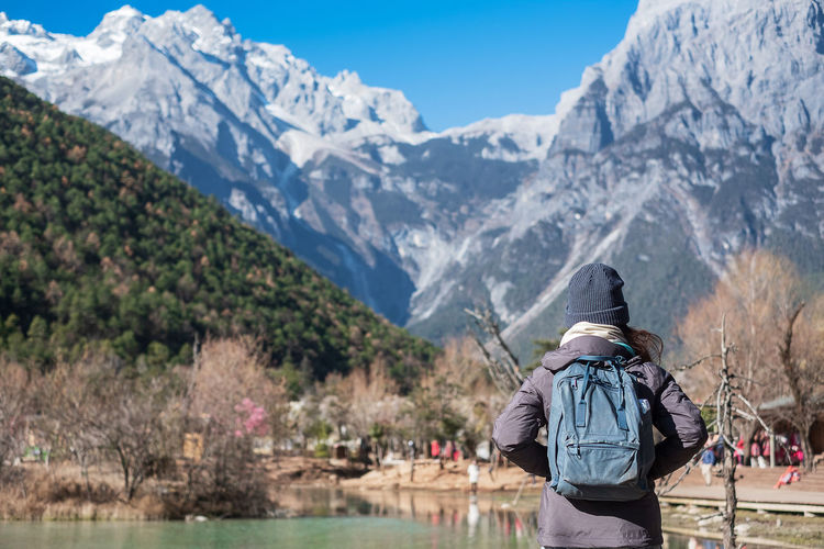 Rear view of woman wearing backpack while standing against mountains during winter