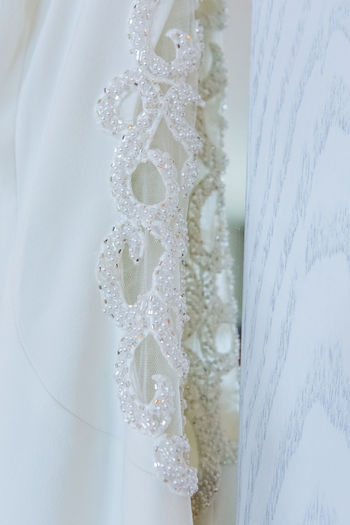 Close-up of white dress hanging by wall