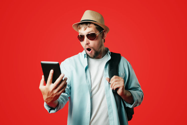 Midsection of man using mobile phone against red background